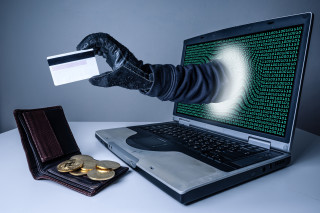 The abstract image of the hacker's hand reach through a laptop screen for stealing credit card in a wallet. the concept of cyber attack, virus, malware, illegally and cyber security.